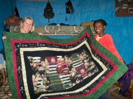 Mary giving a quilt to Fregenet, who shares her top bunk with Tigist.
