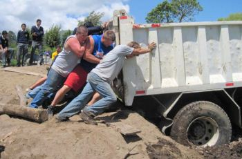 Young men pushing a large dump truck