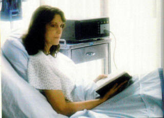 Woman reading Bible in hospital bed