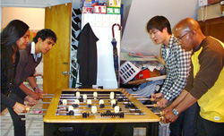 four people playing foosball