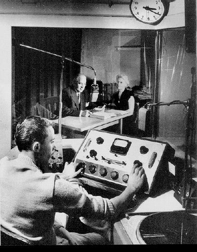 Herbert and Loma Armstrong in a radio studio, with Richard Armstrong at the controls